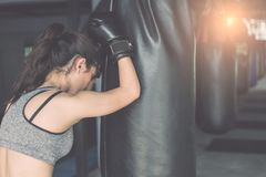 Asian young woman doing exercise with Thai boxing Muay Thai eq. Beautiful asian young woman doing exercise with Thai boxing Muay Thai equipment in gym. Health Stock Image