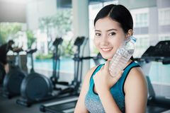 Asian young woman drinking water after exercise in sport club. Asian athlete drinking a bottle of water at the gym. Sport and health care concept Royalty Free Stock Images