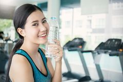 Asian young woman drinking water after exercise in sport club Stock Photos