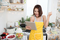 Asian young woman eating healthy food and using a tablet compute Stock Photography