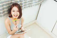 Asian young woman eating healthy food and using a tablet compute. R to cook in her kitchen Stock Photo