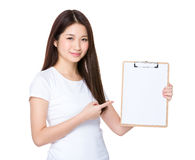 Asian young woman finger point to blank page of clipboard. Isolated on white background Stock Photo