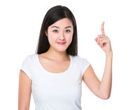 Asian young woman with finger point upwards Royalty Free Stock Photography