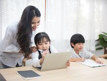 Asian young woman help her son do homework with daughter using laptop sit beside on table in living room at home