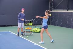 Asian young woman with her trainer practicing outdoor tennis. royalty free stock photo