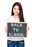 Asian young woman hold with chalkboard showing phrase of back to Stock Image