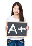 Asian young woman hold with chalkboard showing A plus mark Stock Photo