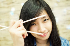 Asian young woman holding chopsticks Royalty Free Stock Photography
