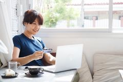 Asian young woman holding credit card and using laptop computer. royalty free stock image