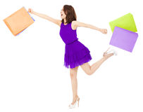 Asian young woman holding shopping bags and running. Royalty Free Stock Photos
