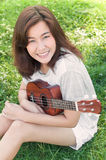 Asian young woman hug her ukulele in the park. Asian young woman hug her ukulele in meadow Royalty Free Stock Photo