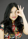Asian young woman looking through finger's hole. Young attractive Asian woman in her 20's shot in studio isolated on a white background Royalty Free Stock Photos