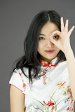 Asian young woman looking through finger's hole. Young attractive Asian woman in her 20's shot in studio  on a white background Royalty Free Stock Image