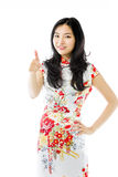 Asian young woman making thumbs up sign standing with hand on hip Royalty Free Stock Images