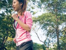 Asian young woman on mark to set ready for jogging exercise to buld up her body on glass in warm light morning. Stock Photo