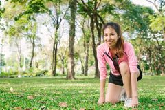 Asian young woman on mark to set ready for jogging exercise to build up her body on glass in warm light morning. Young woman do exercise workout in park to royalty free stock photos