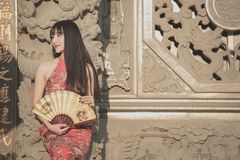 Asian young woman in old traditional Chinese dresses in the Temple.the Temple at Thailand. Asian young woman in old traditional Chinese dresses in the Temple at royalty free stock images
