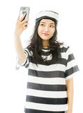 Asian young woman photographing herself with her mobile phone in prisoners uniform Royalty Free Stock Photography