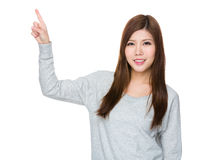 Asian young woman pointing up Stock Images