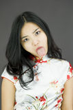Asian young woman poking out tongue towards camera  on colored background Royalty Free Stock Photo