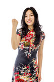 Asian young woman punches fist into the air isolated on white background Royalty Free Stock Images
