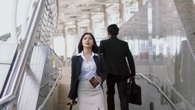 Asian young woman reading the signpost to find destination. Asian young women walks along a baggage with haste reading the signpost to find destination. Blurred Royalty Free Stock Photos