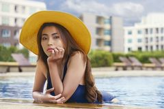Asian young woman relaxing in swimming pool. Enjoying summe royalty free stock image