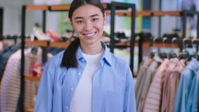 Asian young woman seller in a clothes shop looking straight to the camera portrait she have a large smile and white