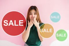 Asian Young Woman in Shocked Surprising Face when Seeing Sale Ta. Gs, Looking at camera and closed mouth with hands, Woman Lifestyle and Shopping Promotion stock images