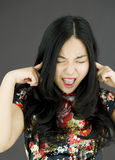 Asian young woman shouting with hands in ear Stock Image