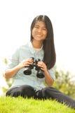 Asian young woman sit on mound seeking binoculars . Stock Images