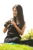 Asian young woman sit on mound seeking binoculars. Royalty Free Stock Photos