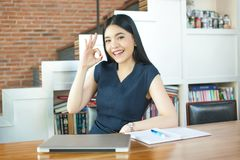 Asian Young Woman sitting with laptop computer and ok sign.  Royalty Free Stock Photos