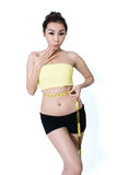 Asian young woman slim fit  is measuring waist on white Studio B Royalty Free Stock Image