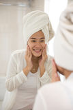 Asian young woman taking care her face with both hands, smile Royalty Free Stock Image