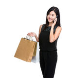 Asian young woman talk on mobile phone with shopping bag Stock Image