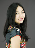 Asian young woman turning back  on colored background Royalty Free Stock Images