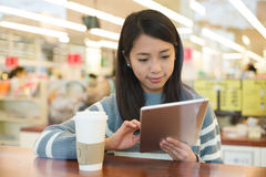 Asian young woman use of tablet pc with cup of coffee Royalty Free Stock Image