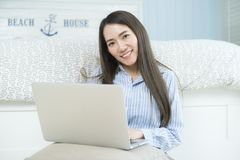 Asian young woman using laptop computer in her bedroom. stock photo