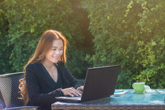 Asian young woman using with laptop. Work business in the garden next to the house in morning holiday, feel happy Royalty Free Stock Photo