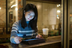 Asian young woman using tablet for online shopping in cafe Royalty Free Stock Photos