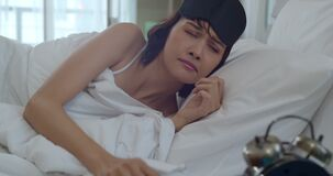 Asian young woman waking and touching alarm clock