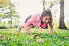 Asian young woman warm up her body by push up to build up her strength before morning jogging exercise. Asian young woman warm up her body by push up to build Royalty Free Stock Photos