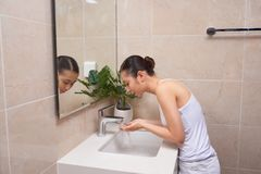 Asian young woman washing her face on the sink.  royalty free stock photo