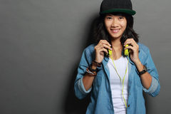 Asian young woman wearing a hat listening to music royalty free stock photo