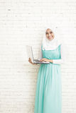asian young woman wearing hijab standing while holding a laptop Stock Photos