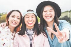 Asian young women friends having fun outdoor - Happy trendy girls laughing together - Millennial generation, bonding, friendship