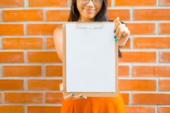 Asian young Women holding clipboard and a blank white paper.  Royalty Free Stock Images