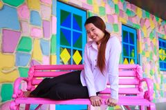 Asian young women sitting on pink chair Royalty Free Stock Images