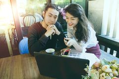 Asian younger freelance man and woman working on computer in home office royalty free stock photography
